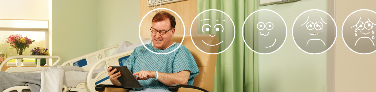Postsurgical male patient smiling happily as he sits up in his hospital room chair on his way to recovery